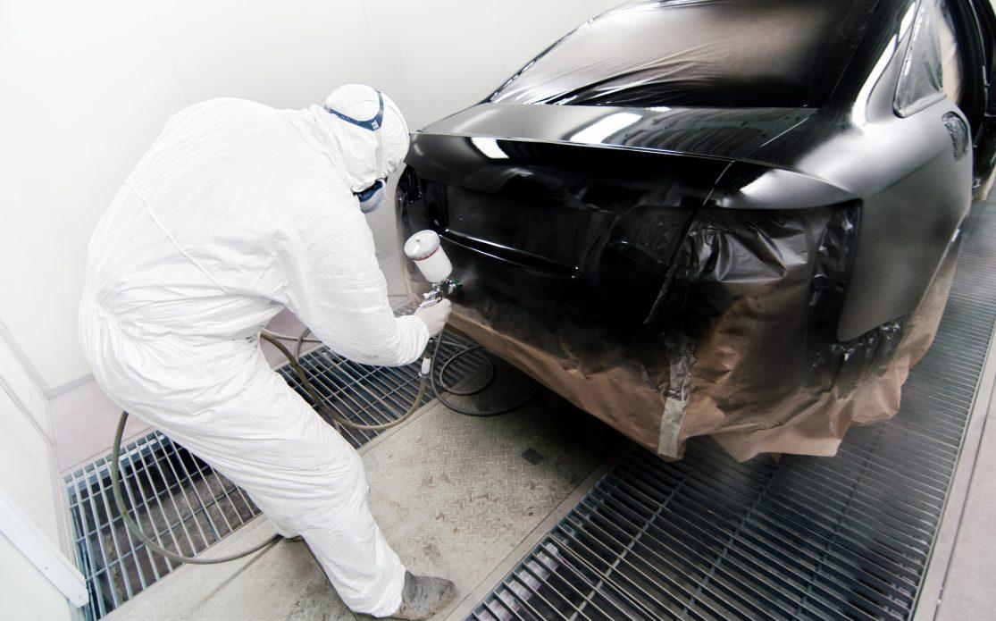 Worker painting a car in garage using an airbrush gun